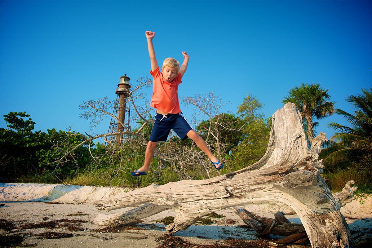 Boy jumping off log at Sanibel Lighthouse Beach.