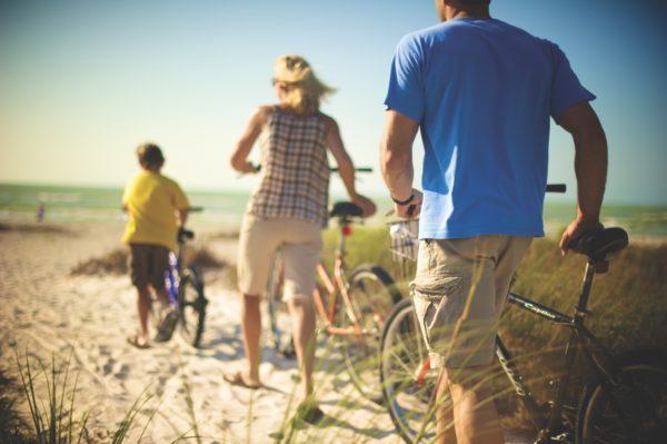 Family walking bikes on beach
