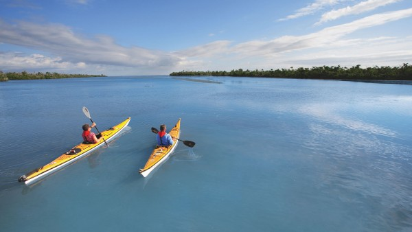 two people in kayaks paddling out by the shoreline