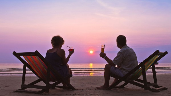couple with beverages watching the sun set on the beach