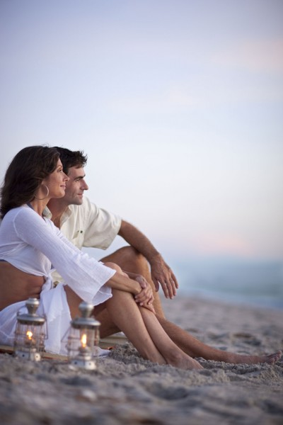 Quiet scene of couple sitting on the beach at sunset